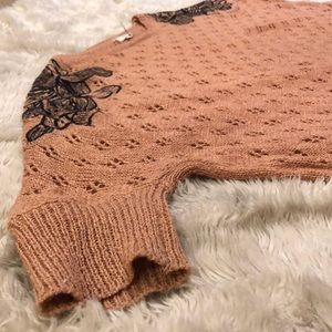 Coral sweater, black floral stitching on shoulders
